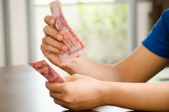 Hand die 100 Thais Bahtbankbiljet, Salaris houden of geld besparen Royalty-vrije Stock Fotografie