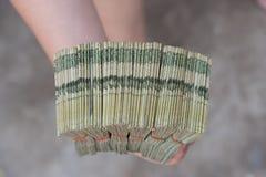 Hand die Thaise bankbiljetten geven Stock Foto's