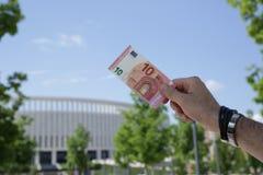 hand die tien euro houden tegen de blauwe hemel en het groene gebladerte royalty-vrije stock fotografie