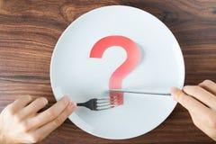 Hand, die Tischbesteck mit einer Frage Mark On Plate hält Stockbild