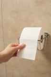 Hand, die Toilettenpapierrolle im Halter zieht Lizenzfreie Stockfotografie