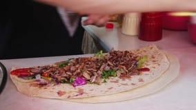 Hand, die traditionelles Shawarma mit Rindfleisch und Gemüse einwickelt stock footage