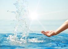 Hand, die Trinkwasser in den Sonnestrahlen spritzt lizenzfreies stockbild