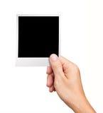 Hand, die unbelegtes sofortiges Foto auf Weiß anhält Stockfoto