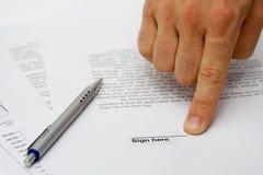 Hand, die Unterzeichnungplatz auf Vertrag zeigt Stockfotografie