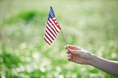Hand, die US-Flagge für Unabhängigkeitstag hält lizenzfreie stockfotos