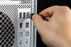 Hand, die USB an den Computer anschließt Stockbilder