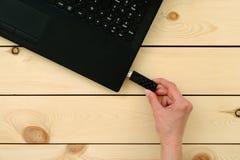 Hand die usb geheugenstok opnemen aan laptop computer stock foto's