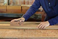 Hand die van arbeider met handplaner aan een plank van hout werken stock foto