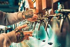 Hand die van barman een groot lagerbierbier in kraan gieten stock foto's