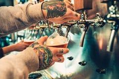 Hand die van barman een groot lagerbierbier in kraan gieten stock foto