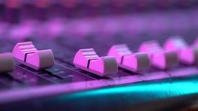 Hand die van correcte ingenieur met fader aan mixerconsole bij muziekoverleg werken Sluit omhoog mening Kleurrijk neonlicht stock video