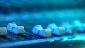 Hand die van correcte ingenieur met fader aan mixerconsole bij muziekoverleg werken Sluit omhoog mening Kleurrijk neonlicht stock videobeelden