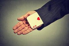 Hand die van de beeld de hogere mens een verborgen aas van de koker terugtrekken Stock Foto
