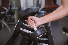 Hand die van de mens een domoor nemen uit reeks zwarte gewichten Royalty-vrije Stock Afbeeldingen