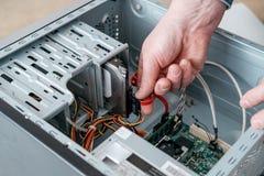 Hand die van de mens SATA-Serie stoppen BIJ Gehechtheid, Serial ATA-gegevenskabel in hard aandrijvingsapparaat De interface van d stock foto's