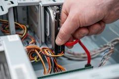Hand die van de mens SATA-Serie stoppen BIJ Gehechtheid, Serial ATA-gegevenskabel in hard aandrijvingsapparaat De interface van d stock foto