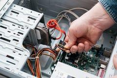 Hand die van de mens SATA-Serie stoppen BIJ Gehechtheid, Serial ATA-gegevenskabel in hard aandrijvingsapparaat De interface van d stock fotografie