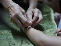 Hand die van oude vrouw een wit koord Sai Sin golven rond haar kleindochterhanden - Thaise traditionele zegen van oudere  royalty-vrije stock fotografie