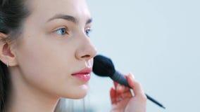 Hand die van professionele grimeur poeder behandelen die pluizig borstelgezicht van jonge mannequin gebruiken stock videobeelden