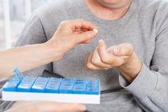 Hand die van verpleegster geduldig medicijn geven Stock Afbeeldingen