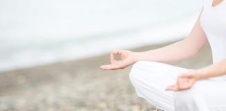 Hand die van vrouw in een yoga de mediteren stelt op strand stock afbeeldingen