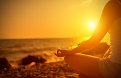 Hand die van vrouw in een yoga op strand mediteren Stock Foto's