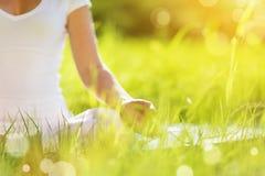 Hand die van vrouw in lotusbloempositie het praktizeren yoga mediteren stock fotografie