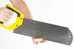 Hand die van werkman houten blok met metaalzaag zagen Stock Afbeeldingen