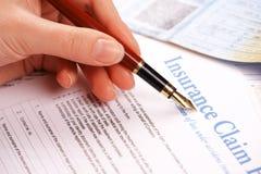 Hand, die Versicherungsleistungenform ausfüllt lizenzfreies stockfoto