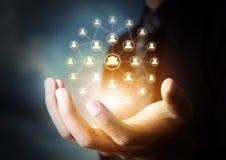 Hand, die virtuelle Ikone des Sozialen Netzes hält Stockfotografie