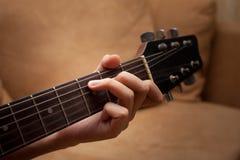 Hand, die Volksgitarre spielt Lizenzfreie Stockfotos