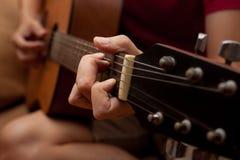 Hand, die Volksgitarre spielt Stockfoto