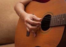 Hand, die Volksgitarre spielt Stockbild