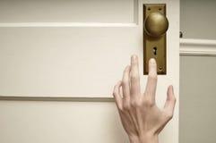 Hand die voor deurknop bereikt stock afbeelding