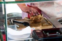 Hand die voor een broodje bereiken dat een lange braadworst houdt royalty-vrije stock foto