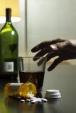 Hand die voor wijn en voorschriftpillen op verticale lijst bereiken, stock foto's