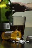 Hand die voor wijn en voorschriftpillen op verticale lijst bereiken, stock foto