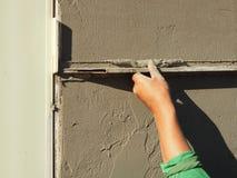 Hand, die Wand mit Kelle vergipst Stockbilder