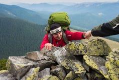 Hand die wandelaar helpen om de berg te beklimmen stock foto