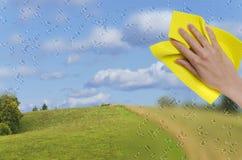 Hand, die weg vom regnerischen Fenster abwischt Lizenzfreie Stockbilder