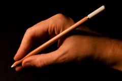 Hand, die weißen Bleistift anhält Stockfotografie