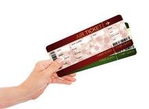 Hand, die Weihnachtsfliegen-Flugtickets über Weiß hält Lizenzfreies Stockfoto