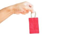 Hand die weinig rode die het winkelen zak houden, op witte achtergrond wordt geïsoleerd stock afbeeldingen
