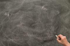 Hand die wit krijt houden en op bord beginnen te schrijven Stock Afbeeldingen