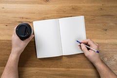 Hand die wit leeg document bladmodel op houten achtergrond houden stock afbeeldingen