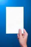 Hand die witte bladdocument kaart op blauw houdt Royalty-vrije Stock Foto's