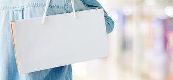 Hand die witte het winkelen zak op de achtergrond van de onduidelijk beeldopslag, banner houden royalty-vrije stock afbeelding