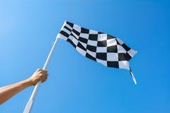 Hand, die Zielflagge auf Hintergrund des blauen Himmels hält Stockfotos