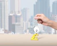 Hand die zilveren sleutel met gouden de vormsleutelring van het dollarteken houden Stock Afbeelding